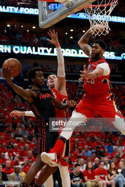 AlFarouq Aminu of the Portland Trail Blazers pass the ball around Anthony Davis of the New Orleans Pelicans during Game 3 of the Western Conference...