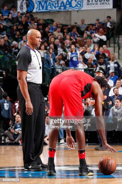AlFarouq Aminu of the Portland Trail Blazers reaches for the ball as Referee Kevin Cutler looks on during the game against the Dallas Mavericks on...