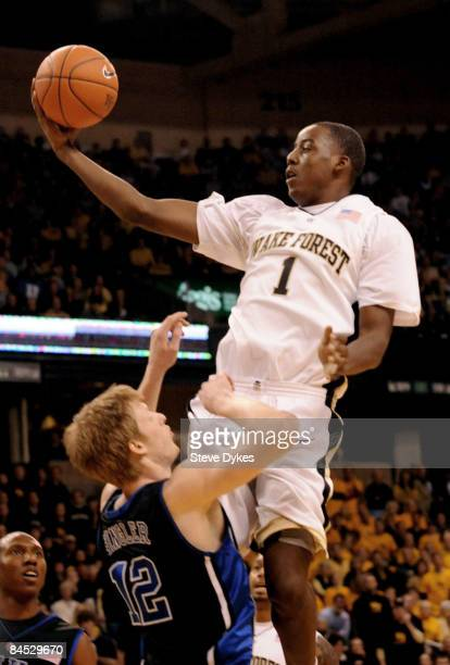 AlFarouq Aminu of the Wake Forest Demon Deacons drives to the basket on Kyle Singler of the Duke Blue Devils during their game at Lawrence Joel...