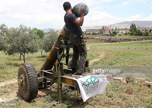 AlFatah forces members load artillery a domestic gas bottle turned into a weapon nicknamed 'hell' before they attack on Syrian regime forces' in the...