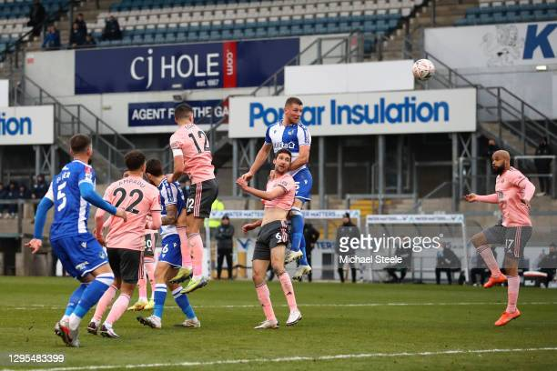 Alfie Kilgour of Bristol Rovers scores their team's first goal under pressure from Chris Basham of Sheffield United during the FA Cup Third Round...