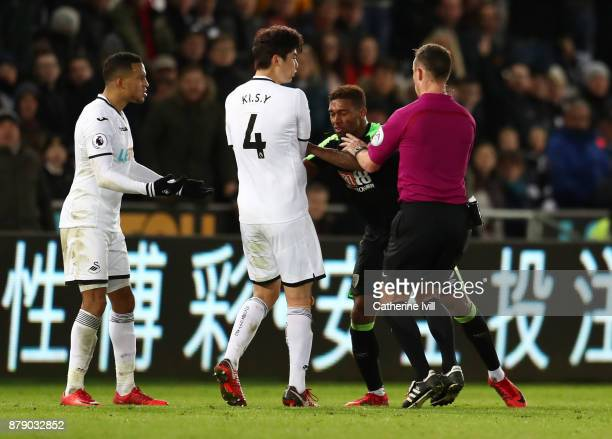 Alfie Mawson and Ki SungYueng of Swansea City clash with Jordon Ibe of AFC Bournemouth during the Premier League match between Swansea City and AFC...