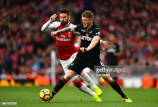 Alfie Mawson of Swansea City and Olivier Giroud of Arsenal battle for possession during the Premier League match between Arsenal and Swansea City at...
