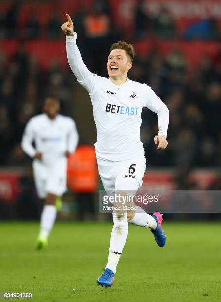 Alfie Mawson of Swansea City celebrates as he scores their first goal during the Premier League match between Swansea City and Leicester City at...
