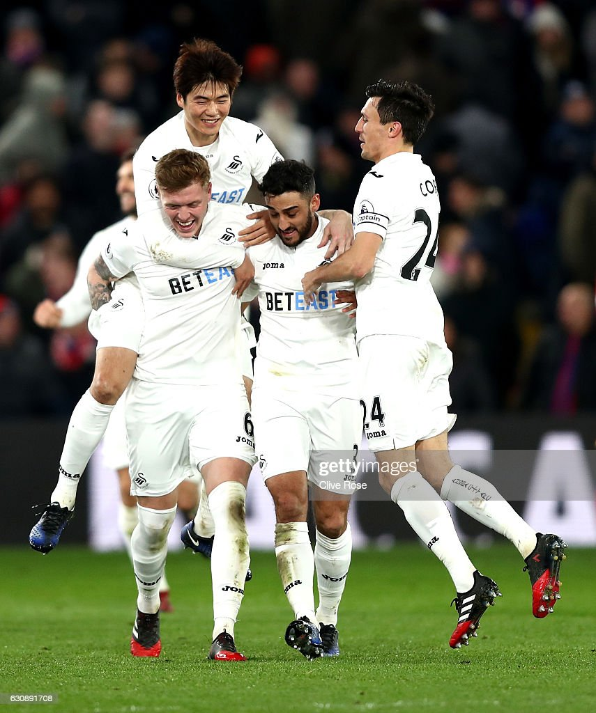 Alfie Mawson (1st L) of Swansea City celebrates scoring the opening goal with his team mates during the Premier League match between Crystal Palace and Swansea City at Selhurst Park on January 3, 2017 in London, England.