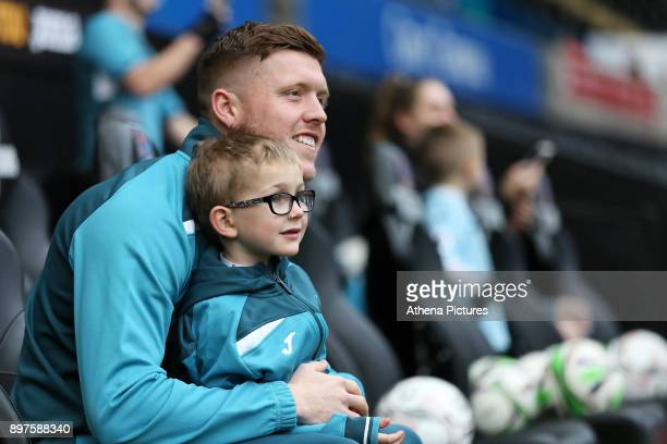 Alfie Mawson of Swansea City embraces a young boy as he arrives prior to the game during the Premier League match between Swansea City and Crystal...