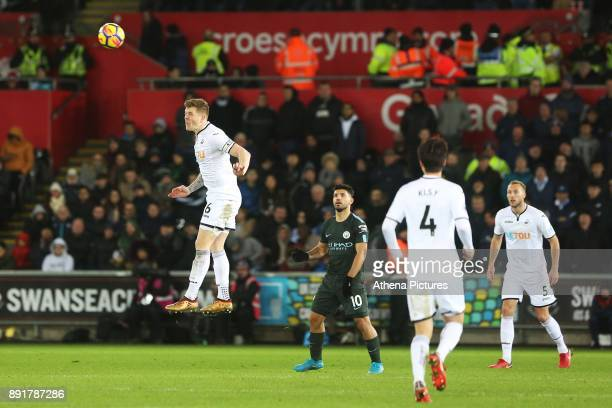 Alfie Mawson of Swansea City heads the ball away during the Premier League match between Swansea City and Manchester City at the Liberty Stadium on...
