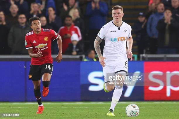 Alfie Mawson of Swansea City is marked by Jesse Lingard of Manchester United during the Carabao Cup Fourth Round match between Swansea City and...