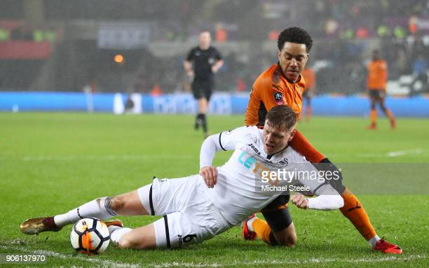 Alfie Mawson of Swansea City is tackled by Helder Costa of Wolverhampton Wanderers during The Emirates FA Cup Third Round Replay between Swansea City...