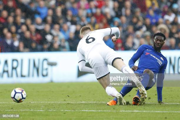 Alfie Mawson of Swansea City is tackled by Tiemoue Bakayoko of Chelsea during the Premier League match between Swansea City and Chelsea at the...