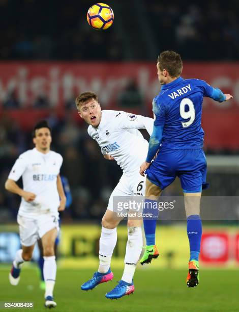 Alfie Mawson of Swansea City jumps with Jamie Vardy of Leicester City during the Premier League match between Swansea City and Leicester City at...
