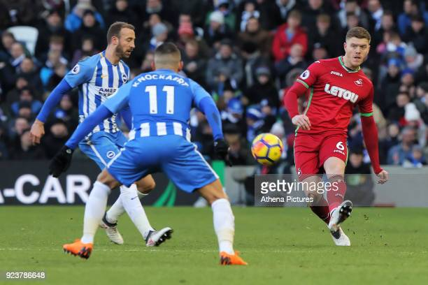Alfie Mawson of Swansea City passes the ball past Glenn Murray and Anthony Knockaert of Brighton during the Premier League match between Brighton and...