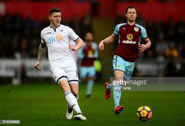 Alfie Mawson of Swansea City passes the ball under pressure from Ashley Barnes of Burnley during the Premier League match between Swansea City and...