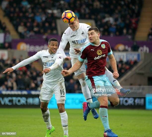 Alfie Mawson of Swansea heads the ball over team mate Matrin Olsson and Sam Vokes of Burnley during the Premier League match between Swansea City and...