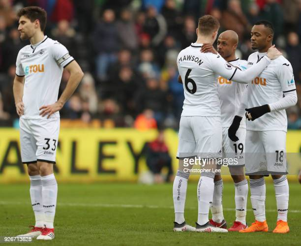 Alfie Mawson speaks with Andre Ayew and Jordan Ayew of Swansea City during the Premier League match between Swansea City and West Ham United at...