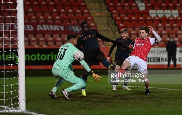 Alfie May of Cheltenham Town scores their team's first goal past Zack Steffen of Manchester City during The Emirates FA Cup Fourth Round match...