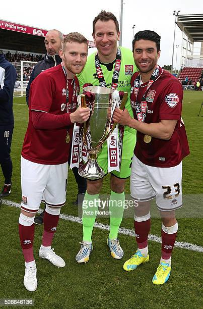 Alfie Potter Ryan Clarke and Danny Rose of Northampton Town celebrate with the Sky Bet League Two champions trophy after the Sky Bet League Two match...