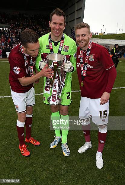 Alfie Potter Ryan Clarke and Lawson D'Ath of Northampton Town celebrate with the Sky Bet League Two champions trophy after the Sky Bet League Two...