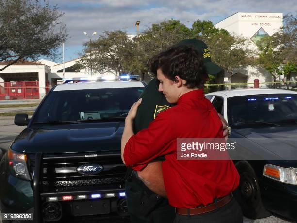 Alfonso Calderon a Junior at Marjory Stoneman Douglas High School hugs Broward County Sheriff officer Brad Griesinger as he guards the front gate of...