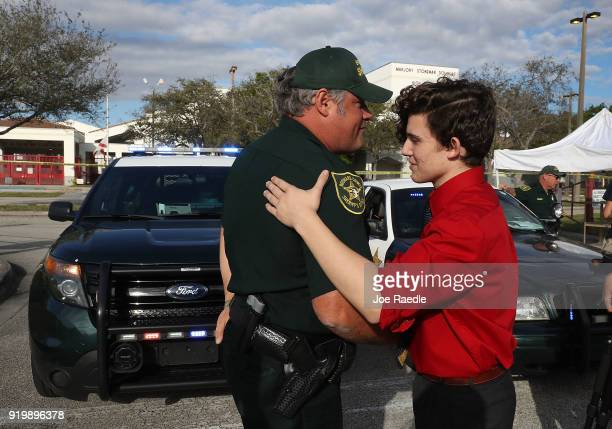 Alfonso Calderon a Junior at Marjory Stoneman Douglas High School speaks with Broward County Sheriff officer Brad Griesinger as he guards the front...
