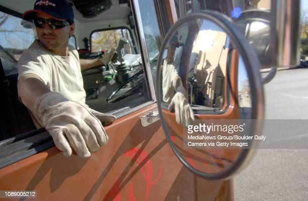 Alfonso Coria a driver for Western Disposal keeps an eye on the trash can loader from the cab of trash pickup truck last Friday in the Table Mesa...