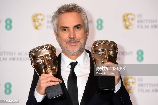 Alfonso Cuaron winner of Best Foreign Language Film and Best Director for the film Roma poses with his awards in the press room during the EE British...
