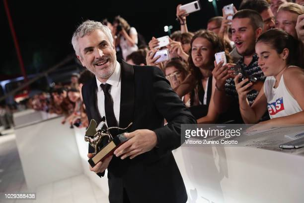 Alfonso Cuaron with the Golden Lion for Best Film Award for 'Roma' walks the red carpet ahead of the Award Ceremony during the 75th Venice Film...