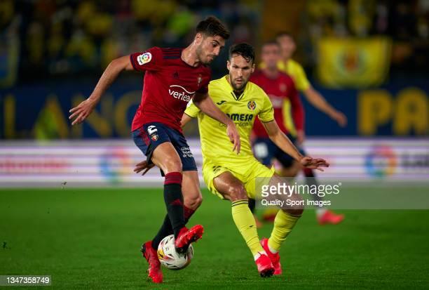 Alfonso Pedraza of Villarreal CF competes for the ball with Nacho Vidal of CA Osasuna during the La Liga Santander match between Villarreal CF and CA...