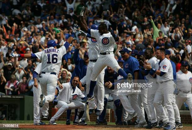 Alfonso Soriano and Cliff Floyd of the Chicago Cubs join the team in welcoming teammate Aramis Ramirez after Ramirez hit a tworun walkoff home run to...