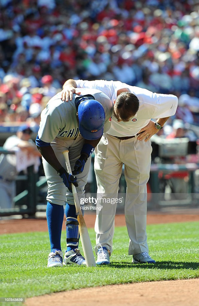 Alfonso Soriano of the Chicago Cubs is checked by the trainer after fouling a ball off his leg during the game against the Philadelphia Phillies at Citizens Bank Park in Philadelphia, Pennsylvania on May 20, 2010. The Phillies defeated the Cubs 5-4.
