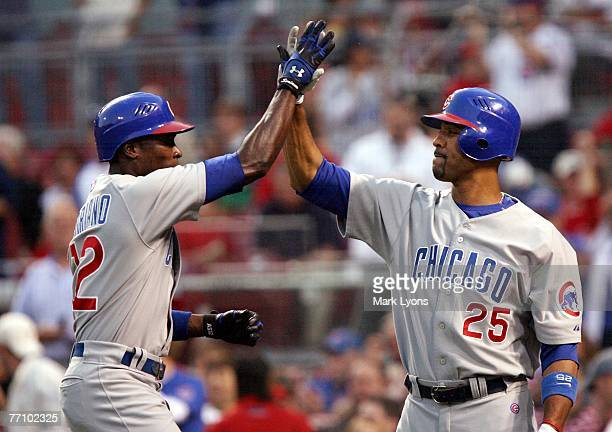 Alfonso Soriano of the Chicago Cubs is congratulated by teammate Derek Lee after hitting a solo home run in the first inning against the Cincinnati...