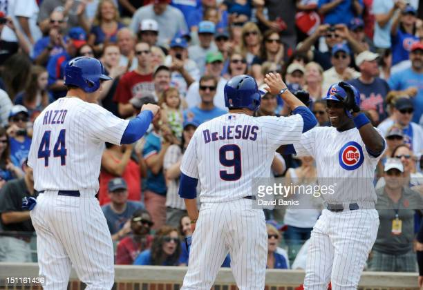 Alfonso Soriano of the Chicago Cubs is greeted by Anthony Rizzo and David DeJesus after hitting a three run homer against the San Francisco Giants in...