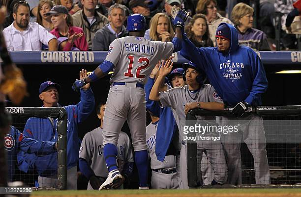 Alfonso Soriano of the Chicago Cubs is welcomed home by pitcher Matt Garza and manager Mike Quade of the Cubs after his solo homerun in the sixth...