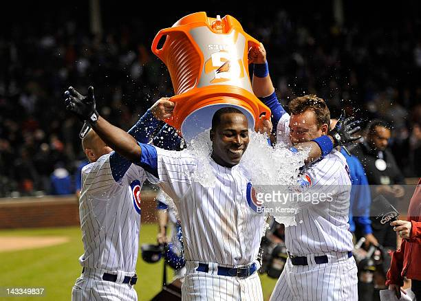 Alfonso Soriano of the Chicago Cubs receives a Gatorade bath from teammates Reed Johnson and Jeff Baker after hitting a gamewinning RBI single...