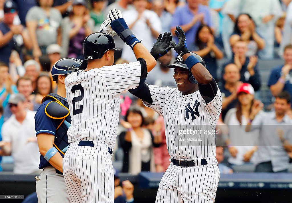 Alfonso Soriano #12 of the New York Yankees celebrates his third inning two run home run against the Tampa Bay Rays with teammate Derek Jeter #2 at Yankee Stadium on July 28, 2013 in the Bronx borough of New York City.