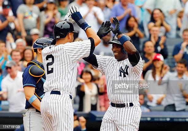 Alfonso Soriano of the New York Yankees celebrates his third inning two run home run against the Tampa Bay Rays with teammate Derek Jeter at Yankee...