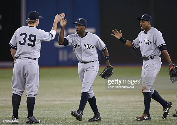 Alfonso Soriano of the New York Yankees celebrates their victory with Mark Reynolds and Curtis Granderson during an MLB game against the Toronto Blue...