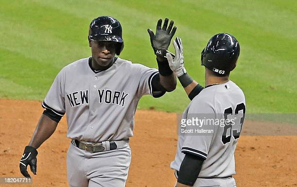 Alfonso Soriano of the New York Yankees is greeted at home plate by Zoilo Almonte after Soriano scored a run in the fourth inning against the Houston...