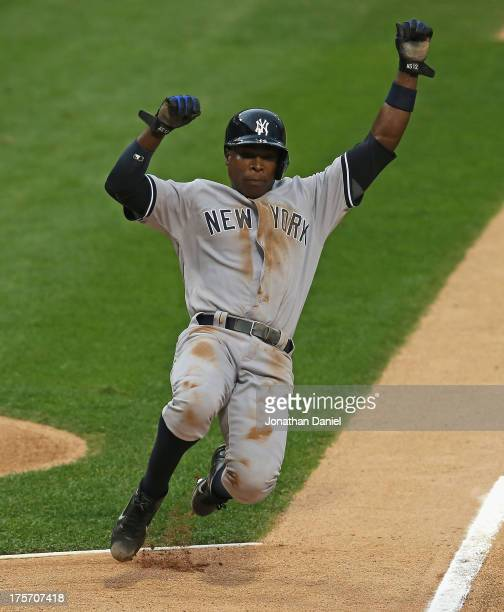 Alfonso Soriano of the New York Yankees slides into home to score a run on a wild pitch in the 1st inning against the Chicago White Sox at US...
