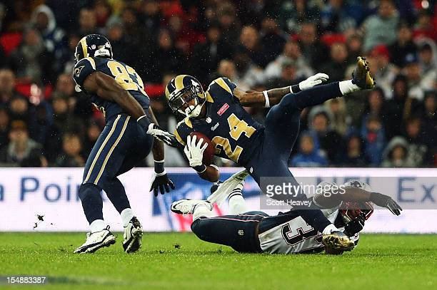 Alfonzo Dennard of the New England Patriots tackles Isaiah Pead of the St Louis Rams during the NFL International Series match between the New...