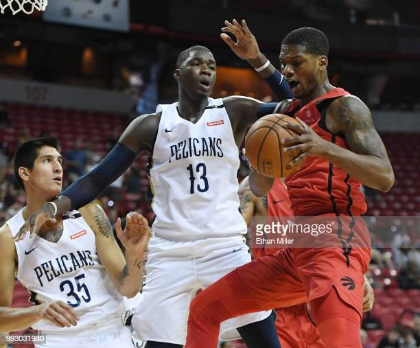 Alfonzo McKinnie of the Toronto Raptors grabs a rebound against Derek Willis and Cheick Diallo New Orleans Pelicans during the 2018 NBA Summer League...
