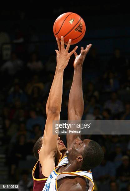 Alfred Aboya of the UCLA Bruins and Jeff Pendergraph of the Arizona State Sun Devils reach for the opening tip off during the college basketball game...
