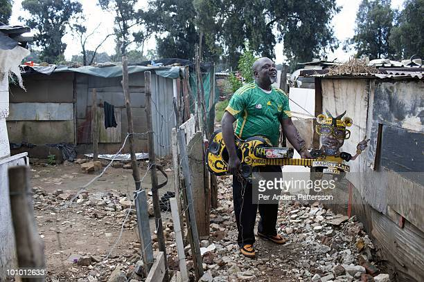 Alfred Baloyi an artist and the founder of the Makarapa Helmet stands outside his old studio wearing one of his older creations a guitar makarapa in...