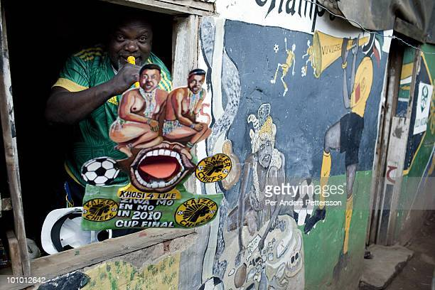 Alfred Baloyi an artist and the founder of the Makarapa Helmet stands in his old studio in a squatter camp blowing a Vuvuzela trumpet in Primrose...
