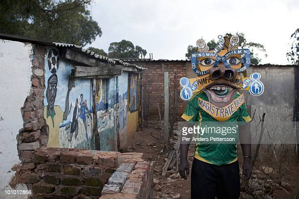 Alfred Baloyi an artist and the founder of the Makarapa Helmet stands outside his old studio in a squatter camp with one of his early Makarapas in...