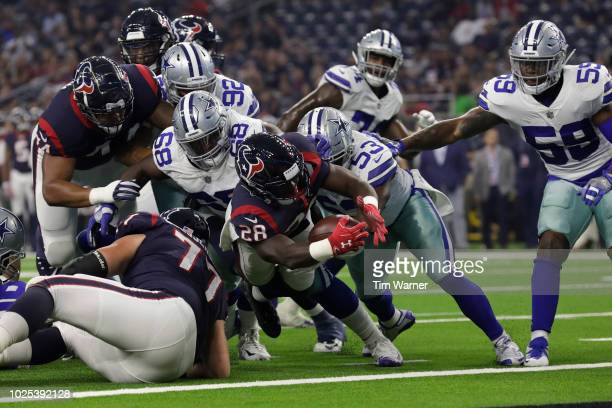 Alfred Blue of the Houston Texans dives across the goal line for a touchdown defended by Justin MarchLillard of the Dallas Cowboys and Daniel Ross in...