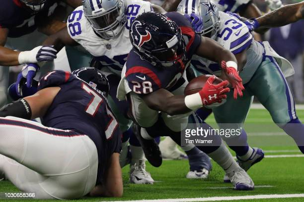 Alfred Blue of the Houston Texans dives for a touchdown defended by Daniel Ross of the Dallas Cowboys and Justin MarchLillard in the first half of...