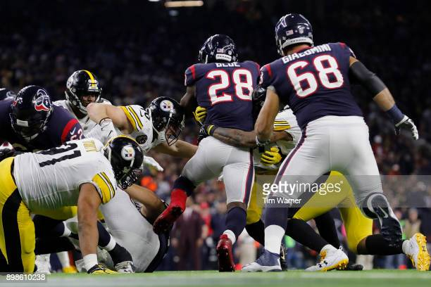 Alfred Blue of the Houston Texans is tackled by Bud Dupree of the Pittsburgh Steelers and TJ Watt in the third quarter at NRG Stadium on December 25...