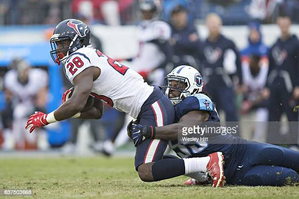 Alfred Blue of the Houston Texans is tackled by Sean Spence of the Tennessee Titans at Nissan Stadium on January 1 2017 in Nashville Tennessee The...