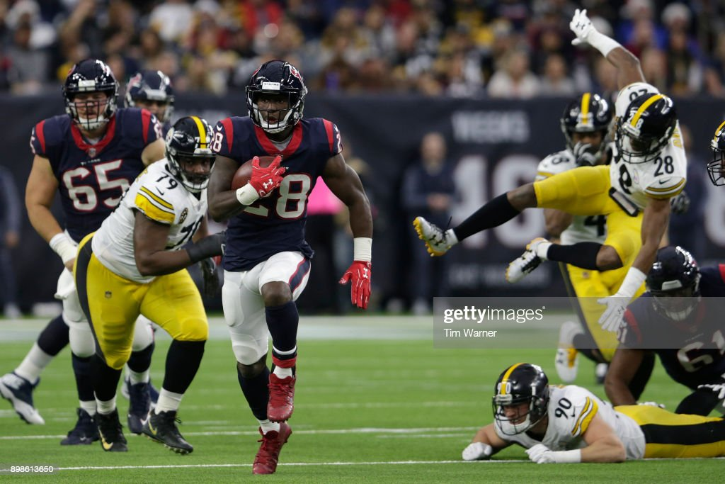 Alfred Blue #28 of the Houston Texans runs the ball in the first half pursued by Javon Hargrave #79 of the Pittsburgh Steelers and Sean Davis #28 at NRG Stadium on December 25, 2017 in Houston, Texas.
